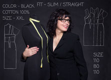 Adult tailor with mannequin on black background with task Stock Images