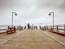 Adult tall man on pier board look over sea to morning fall horizon. Smooth water level Stock Images