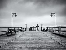 Adult tall man on pier board look over sea to morning fall horizon. Smooth water level Stock Photos