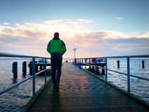 Adult tall man on pier board look over sea to morning Sun. Smooth water level Stock Photos