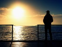 Adult tall man on pier board look over sea to morning Sun. Smooth water level Royalty Free Stock Photo