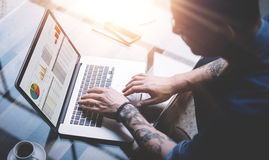 Adult tattooed coworker using laptop while working at sunny office.Graphs and diagramm on notebook screen.Blurred Stock Image