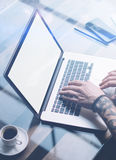 Adult tattooed coworker working on laptop with white blank computer screen at sunny office.Businessman typing on. Notebook keyboard.Vertical mockup,blurred stock photo