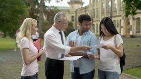 Adult teacher returning tests with marks to multi-ethnic students, good results royalty free stock images