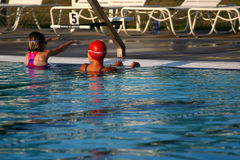 Adult teaching child to swim. Woman and girl at the edge of a pool , woman is teaching girl backstroke racing tips Stock Photos