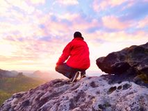 Adult tourist in black trousers, red jacket and dark cap sit on cliff edge and looking to valley Royalty Free Stock Photo