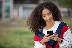 Beautiful ethnic model using phone outside stock images