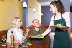 Adult waitress taking order at table Stock Photography