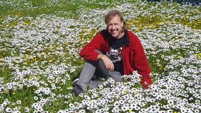 Adult white male wearing a red jacket seated in a field of daisies Royalty Free Stock Image