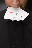 Adult white man hold in mouth  ace cards Royalty Free Stock Photo