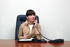 Adult white woman behind a desk in an office talking on. Adult white happy female in a white and roomy office talking on the phone and sitting behind a big brown royalty free stock photos
