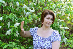 Adult woman with allergic diseases removed from wild cherry blossoms Royalty Free Stock Photography