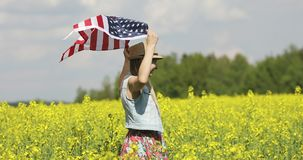 An adult woman with an American flag with pole, stars . An adult woman with an American flag with pole, stars and stripe walks in a flowering rapeseed field stock video footage