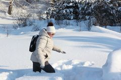 Adult woman with a backpack going on deep snow in the forest Royalty Free Stock Photo