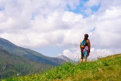 An adult woman with a backpack stands with her back to the camera on the green grass in the mountains royalty free stock photo