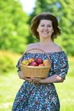 Adult woman with a basket of fruit in the park Royalty Free Stock Photos