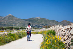 Adult woman is biking at Favignana Island, Italy royalty free stock photography