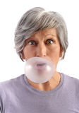 Adult Woman Blowing Chewing Gum. Adult Woman with Short Gray Hair Blowing Chewing Gum with Eyes Wide Open Looking at Camera. Isolated on White Background royalty free stock photography