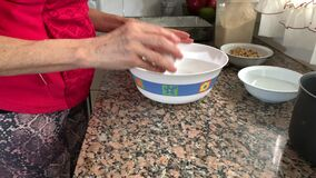 Adult woman breaking up two eggs and putting them in a bowl. Indoor activity to stay in concept house after coronavirus quarantine.  stock video
