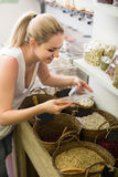 Adult woman buying dried beans by weight Stock Photography