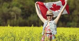 An adult woman with a Canadian flag dances in a rapeseed field in summer. Flag of Canada fluttering in the wind stock video