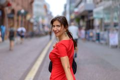 Adult woman looking over shoulder at camera. Adult woman carrying bag looking over shoulder at camera and walking along street filled with blurred people royalty free stock image