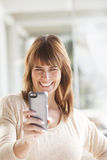 Adult woman with cell phone. Adult woman smiling with cell phone Royalty Free Stock Photo