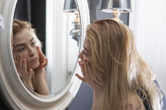 Adult woman checking her face in mirror stock photo