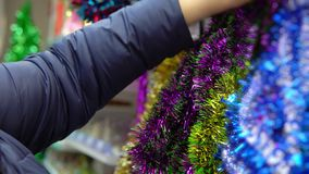 Woman chooses Christmas holiday decorations in the mall. An adult woman chooses Xmas toys and tinsel in the mall, she buys the festive attributes in front of stock video
