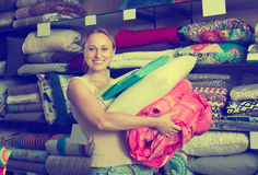 Adult woman choosing blanket and pillow. Portrait of adult woman choosing blanket, pillow and textile in bedding section in shop Stock Photos