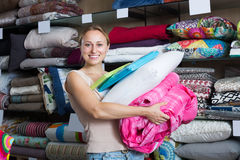 Adult woman choosing blanket and pillow Stock Photos