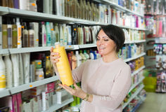 Adult woman choosing hair care products. In shop and smiling stock images