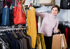 Adult woman choosing turtleneck sweater Stock Images