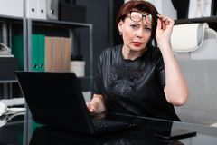 Stylish woman lifted her glasses and looks right sitting at table in office. Adult woman at computer. portrait of Strict businesswoman holding hand glasses for stock photos