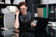 Stylish woman lifted her glasses and looks right sitting at table in office. Adult woman at computer. portrait of Strict businesswoman holding hand glasses for royalty free stock photo