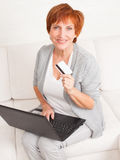 Adult woman with credit card and laptop Royalty Free Stock Photos