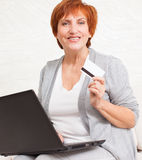 Adult woman with credit card and laptop Stock Photos
