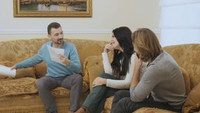Adult woman cries during psychologist`s reception. Married couple sits on the sofa in the room at a psychologist`s reception. The woman cries and the stock footage