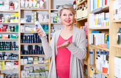 Adult woman customer browsing rows of skin care products Royalty Free Stock Image