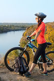 Adult woman cyclist admiring the landscape. Royalty Free Stock Images