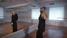 Adult woman is dancing in front of a mirror in the studio after a hard day`s work. Hobbies of ordinary housewife. Training of modern dance in large dance stock video