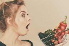 Woman with vegetables, shocked face expression. Adult woman do not like to eat raw food, questioning healthy lifestyle recommendations, origin vegetagles. Female stock photography