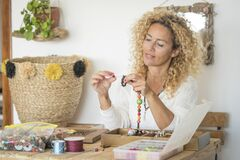 Free Adult Woman Doing Hand Made Creations Jewelry At Home With Colorful Beads And Cords - Female People Working At Home For Online Stock Image - 216667821