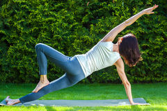 Adult woman doing yoga on green grass Royalty Free Stock Photography