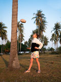 Adult woman in dress standing under a palm tree and catches a coconut Stock Photo