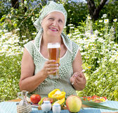 The adult woman drinks the fresh cooled dark barle Royalty Free Stock Image