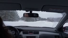 Woman driving car on crossroad and snowy road at winter day view from back seat
