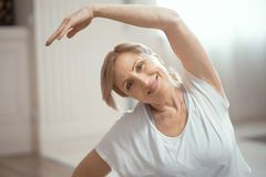 Yoga Classes at Home Beautiful Women Over 50 Years. An Adult Woman of About 50 Enjoys Yoga. She Conducts Classes at Home. Yoga Improves Her Mood. Close Up Shot royalty free stock photography