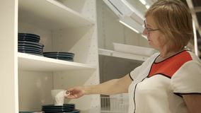 An adult woman examines cups and plates in the mall, she needs dishes stock video