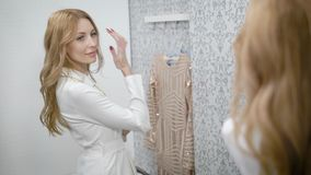 Adult woman is fitting white trendy jacket in a changing room in mall, looking on herself in mirror. View of her reflection stock video footage